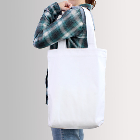 Girl is holding white blank cotton tote bag, design mockup. Handmade shopping bag for girls. Imagens