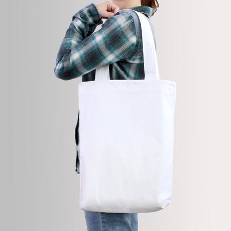 Het meisje houdt witte lege katoenen draagtas, ontwerp mockup. Handgemaakte boodschappentas voor meisjes. Stockfoto