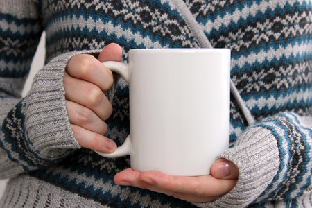 Girl in a warm cardigan is holding white mug in hands. Mockup for winter gifts design. Banque d'images