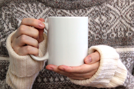 Girl in a warm sweater is holding white mug in hands. Mockup for winter gifts design. Stockfoto