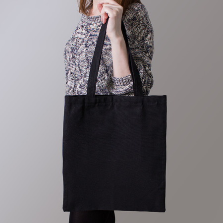 Mock-up. Girl is holding black cotton tote bag. Handmade eco shopping bag for girls.