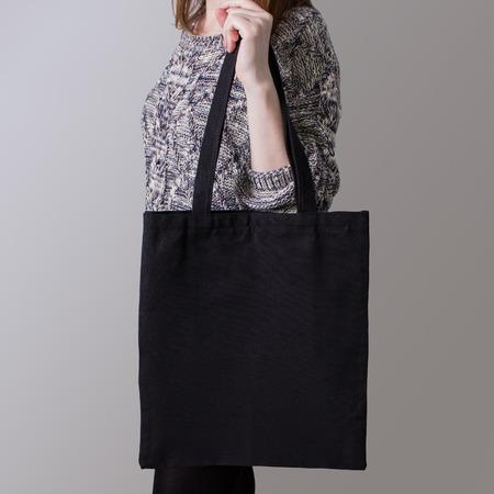 linen bag: Mock-up. Girl is holding black cotton tote bag. Handmade eco shopping bag for girls.