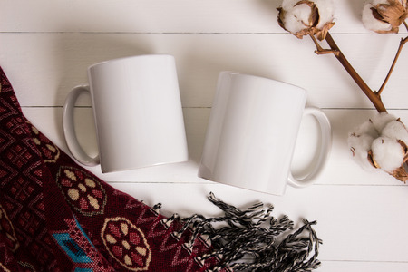 Two white mugs, pair of cups, Mockup. Cozy atmosphere, wooden background, cotton and wool decorations for winter gifts. Banco de Imagens - 69107082