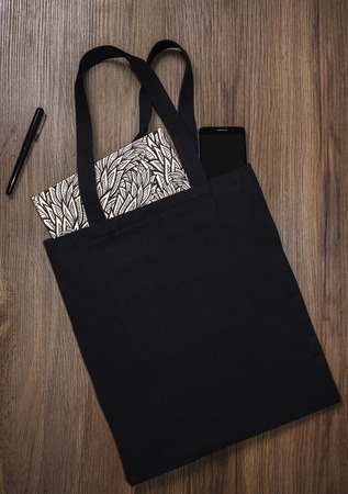 Black blank cotton eco tote bag with smartphone and notebook, design mockup.