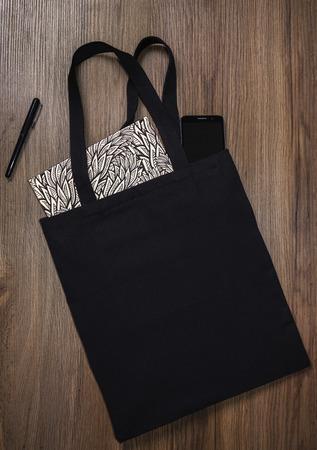 Zwarte lege katoenen eco draagtas met smartphone en notitieboekje, ontwerpmodel.