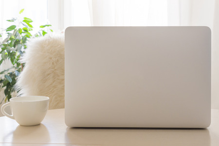 Cozy workplace with modern Laptop and white cup. Mockup, trendy photography