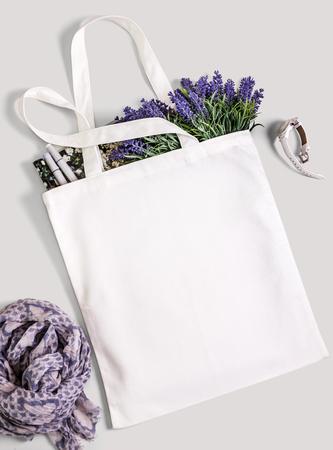 라벤더 꽃, 잡지, 시계, 스카프와 흰색 빈 면화 에코 토트 백. 디자인 모형.