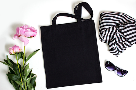Black blank cotton eco tote bag with pink peony, glasses and scarf, design mockup.