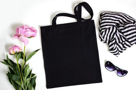 Sac fourre-tout écologique en coton noir avec pivoine rose, lunettes et écharpe, maquette.