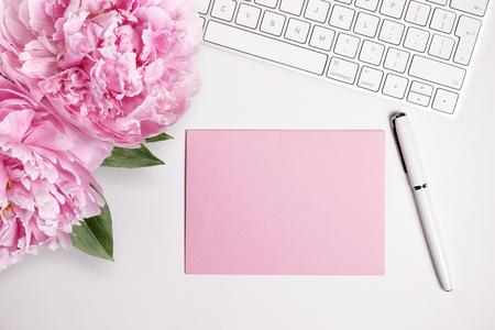 흰색 키보드와 핑크 모란, 상위 뷰 여성의 데스크탑을 조롱. 텍스트 또는 메시지 카드