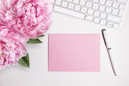 Female desktop with white keyboard and pink peonies, top view mock up. Card for text or message