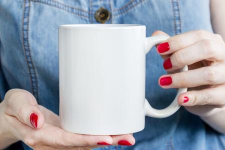 La muchacha está sosteniendo la taza blanca, taza en manos. Maqueta para presentaciones de productos. Foto de archivo - 83704917