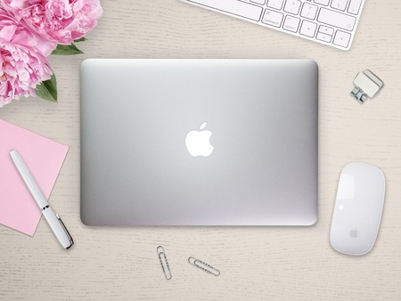 Apple Macbook Pro Retina cover on a desk, table with mouse and stationery. Mockup for cover, decal, sticker design. Trendy office, freelance workplace, top view. Light wooden background.