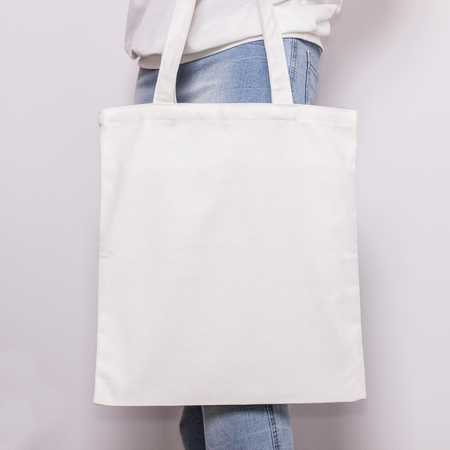 Girl in blue jeans holds blank cotton eco tote bag, design mockup. Handmade shopping bag for girls. Archivio Fotografico