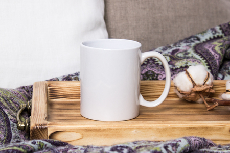 White mug on a wooden tray, the Mockup. Cozy home, linen and wool decorations