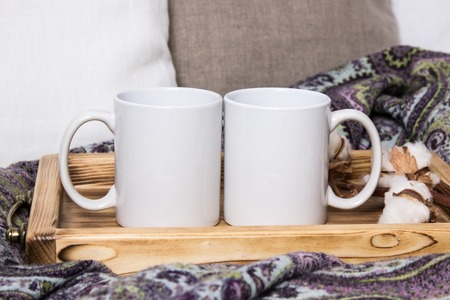 Two white mugs, pair of cups on a wooden tray, the Mockup. Cozy home, wooden background, cotton and wool decorations, winter gifts Archivio Fotografico