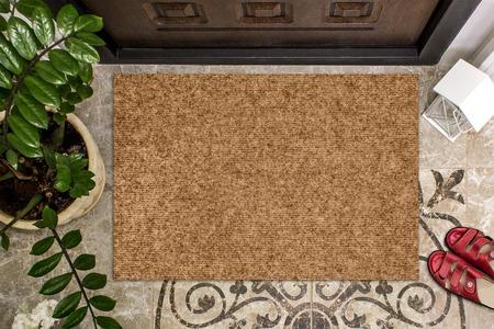 Leere Fußmatte vor der Tür in der Halle. Matte auf Keramikboden, Blumen und roten Schuhen. Willkommen zu Hause, Produkt Mockup Standard-Bild
