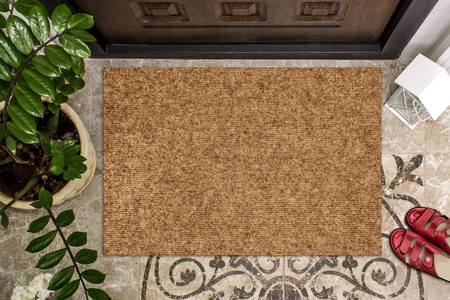 Blank doormat before the door in the hall. Mat on ceramic floor, flowers and red shoes. Welcome home, product Mockup Stockfoto