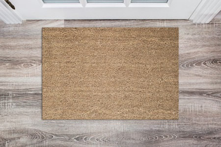 Pusta, jasnobrązowa wycieraczka z włókna kokosowego przed białymi drzwiami w korytarzu. Mata na podłogę drewnianą, produkt Mockup
