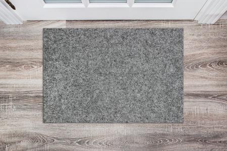 Blank grey woolen doormat before the white door in the hall. Mat on wooden floor, product Mockup
