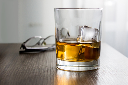 Glass of whiskey, brandy, cognac with ice cubes on wooden table desk with glassess. Mockup of product, gift for man Stock Photo