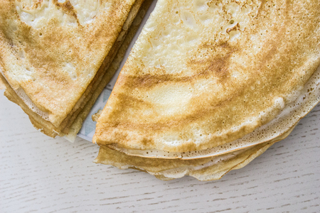 Close up top view of french crepes, thin pancakes on a wooden table