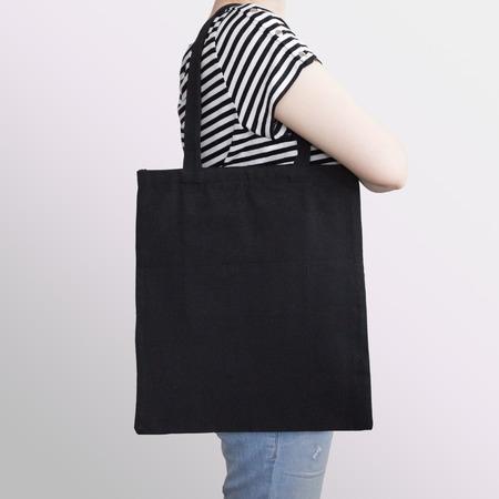 Girl is holding black cotton eco tote bag, design mockup.