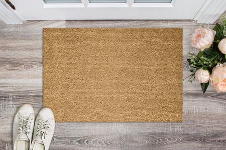 Leere Fußmatte aus Kokos vor der Tür im Flur. Matte auf Holzboden, Blumen und Schuhen. Willkommen zu Hause, Produktmodell
