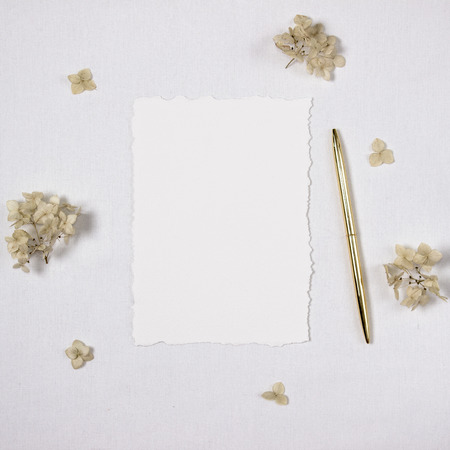 Mock-up of wedding invitation, sheet of paper with torned edges on a white cotton surface and a golden pen, some flowers for decoration.