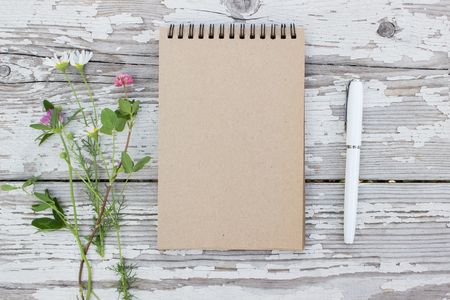 Kraft paper spiral notebook, white pen and summer flowers on rustic wooden background. Mock-up