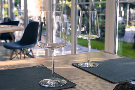 Empty wine glasses on the table in restaurant. Vintage styled photography, product mock-up