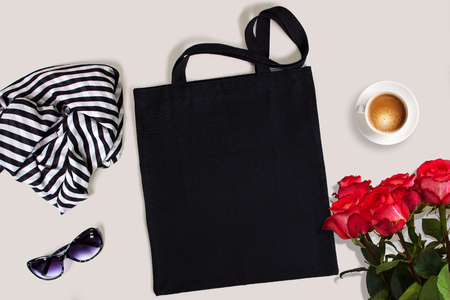 Black blank cotton eco tote bag with red roses, glasses, scarf and a cup of coffee, styled design mockup