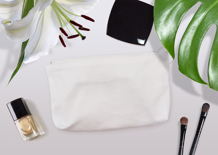 Cosmetic bag mock-up surrounded by make-up stuff and tropical plants