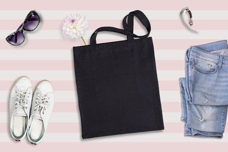 Black tote bag mockup, flat lay on summer style background