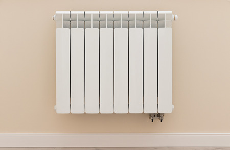 Modern white heating radiator on the wall in apartment room, front view Banco de Imagens