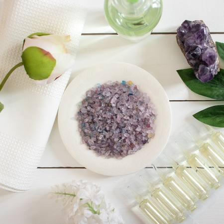 Colourful sea salt with cosmetic oils and white towel