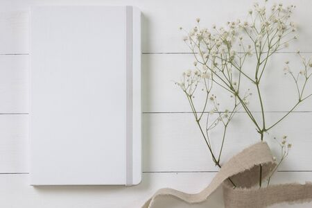 Mock-up of a white notebook, diary. Styled photo with flowers on the light boards Stock fotó