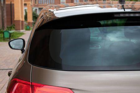 Ventana trasera de un coche aparcado en la calle cerca de casas, vista trasera. Maqueta para calcomanías o calcomanías
