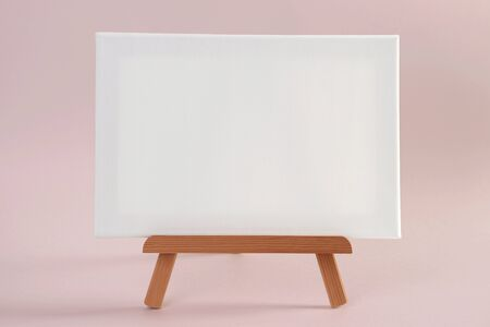 White canvas on small wooden easel, mock-up.