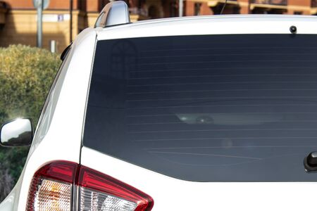 Back window of a white car parked on the street near houses, rear view. Mock-up for sticker or decals