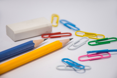 Pencil placed on a white background With an eraser placed next to it and many colors of clips