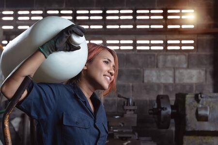 Giovane donna asiatica diversificata che consegna una bottiglia d'acqua sulla spalla - agente di consegna ispanico femminile che arriva in fabbrica con ordine di inventario all'ingrosso - concetto di immigrato, poco qualificato e sul posto di lavoro