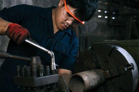 Ingegnere meccanico asiatico che utilizza una macchina per tornio industriale - Formazione per tirocinio millenario su attrezzature per la fabbricazione di produzione - Operaio di fabbrica immigrato ispanico specializzato diversificato in officina