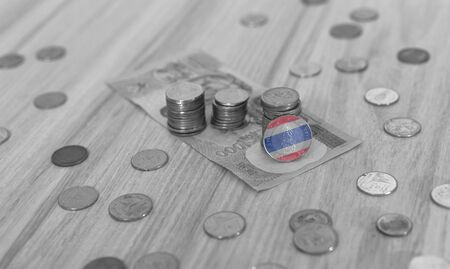 Thailand financial economic concept with stacked coins and notes in mono tone black and white with Thai flag colours on coin