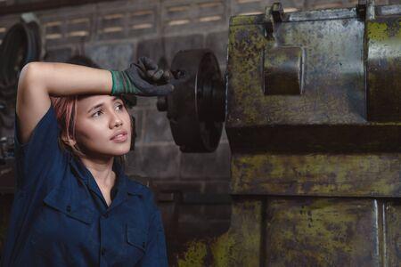 Giovane ingegnere asiatico donna esausta per il carico di lavoro straordinario che lavora in una fabbrica industriale