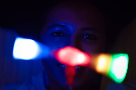 Young woman playing with disco party lights at night - Millennial lifestyle girl at music festival using spinning glowing LED toy - Concert, nightclub and phototherapy concept