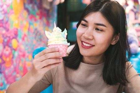 Happy young American Asian girl, eating multicolour unicorn cupcake in trendy city cafe - Fashionable, lifestyle food blogger woman smiling inside a rainbow cake - Colourful dessert concept with faded tint filter