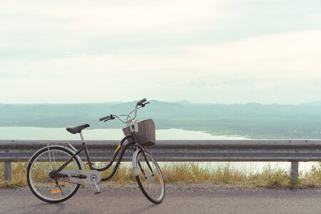 Stationary bicycle on cycle path with amazing scenic views of a lake and mountains - Bike with basket parked next to a cliff edge with epic landscape scenery and warm summer filter - image