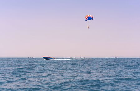 Ocean view of a man Parasailing in the sea towed by a speedboat in american colors - Watersports summer activity of a boat parasail above water with USA stars and stripes