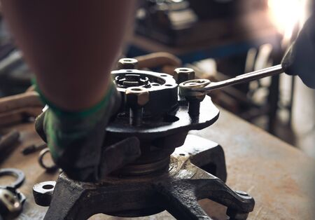 View of engineers hands, adjusting and overhauling used vehicle car parts and recycling scrap metal waste
